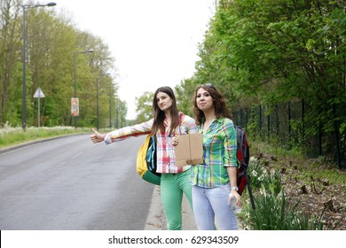 young people tourists hitchhiking along a road