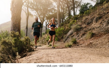 Young people trail running on a mountain path. Two runners working out in morning.