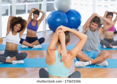 Young people with trainer stretching hands behind backs in a bright gym