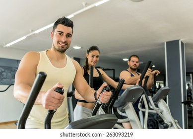 Young people training in eliptical exercises at gym