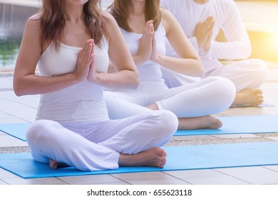 Young people training yoga and meditation at poolside