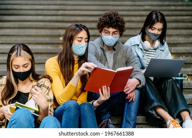 Young people university studyng indoor during coronavirus pandemic. A three women and a young curly man sitting on the stairs of the university for teamwork. Multinational team.
