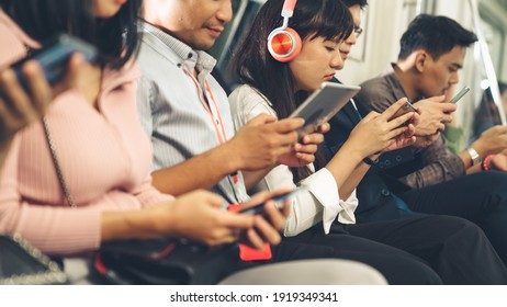 Young people using mobile phone in public underground train . Urban city lifestyle and commuting in Asia concept .