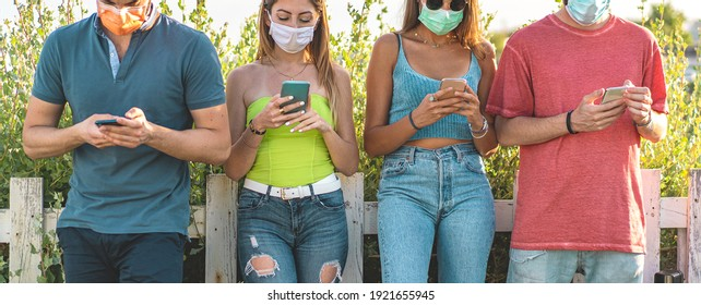 Young people using smart phones watching social media content online wearing face masks against coronavirus pandemic. New normal technology concept.