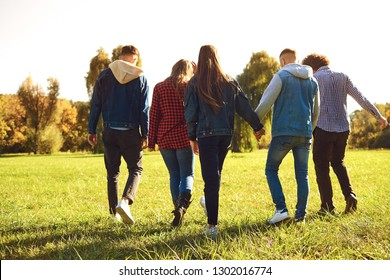 Young people walk in the park in spring.