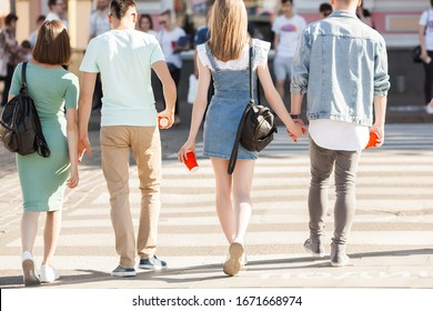Young people walking around the city. Stylish friends together having fun. Group of people drinking coffee and talking.