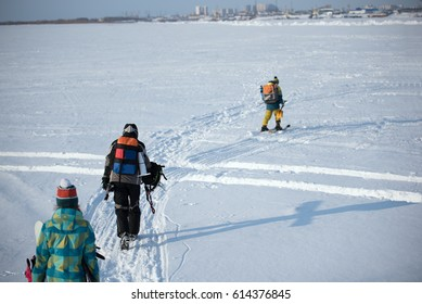 Young people walking on snow on a Sunny day. One on skis. With a bear backpacks.