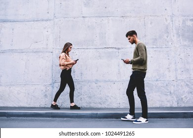 Young people walking on street near publicity area concentrated on technology spending time online, male and female hipsters strolling with smartphones addicted to social networks and digital devices