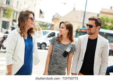 Young people walking and talking on the street in the city.