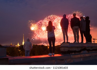 Young people watch fireworks on the roof in Saint-Petersburg, Russia