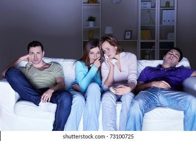 Young people watch a sad movie at home