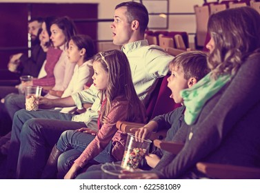 Young people watching exciting movie in cinema house