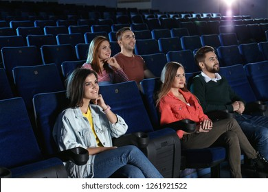 Young people watching movie in cinema theatre