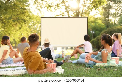 Young people watching movie in open air cinema. Space for text