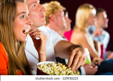 young people watching movie at movie theater