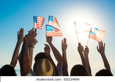 Young people waving American flags at sunset. Guys and girls with American flags. Patriotic party. Flags  flutters in the wind.