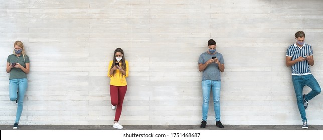 Young people wearing face mask using mobile phone keeping social distance - Millennial friends watching media trends on smartphones during corona virus outbreak - Youth and technology concept