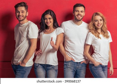 Young people in white t shirts and jeans are looking at camera and smiling, standing against red background. Girl is showing Ok sign