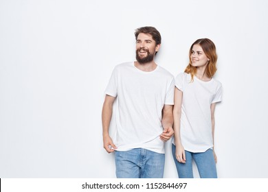 young people in white T-shirts and jeans on a light background