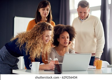 Young people working in office, gathered around laptop