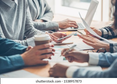 Young people working together at office having business meeting table close-up browsing digital devices drinking hot coffee taking notes