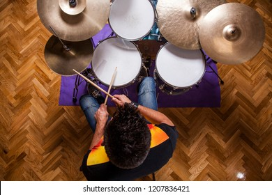 young percussionist rehearsing playing the drums in rehearsal studio, aerial view