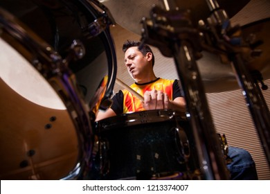 young percussionist rehearsing playing the drums in rehearsal studio, sight through the drums