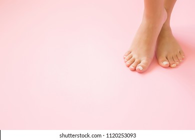 Young, perfect groomed woman's feet on pastel pink background. Care about nails and clean, soft, smooth body skin. Pedicure and manicure beauty salon. Copy space. Empty place for text or logo.