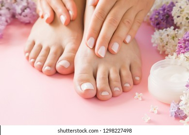 Young, perfect, groomed woman's hands touching her feet on pink floor. Care about nails and clean, soft, smooth legs skin. Beautiful branches of fresh, colorful lilac flowers. Front view. Close up.
