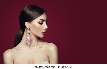 Young perfect woman with makeup, healthy hair, fashion jewelry earrings on red background. Earrings with pearls and feathers