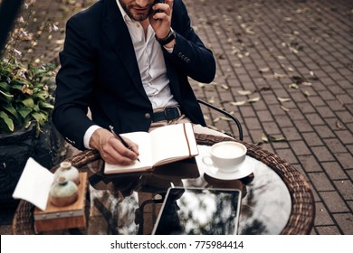 Young perfectionist. Close up top view of young man in smart casual wear talking on his smart phone and writing something down while sitting in restaurant outdoors