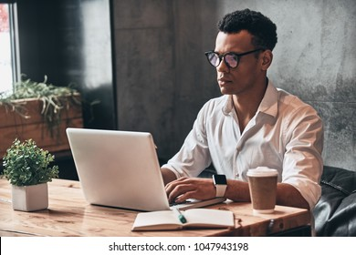 Young perfectionist. Handsome young African man in eyewear working using laptop while sitting in the office
