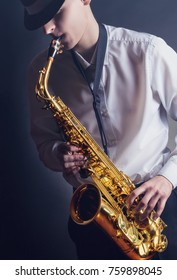 Young performer playing the saxophone against a dark background