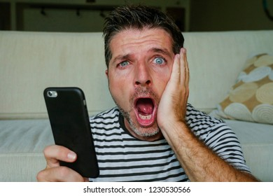 young perplexed and shocked man using mobile phone looking internet social media or checking news in surprised and crazy disbelief face expression feeling petrified and anxious
