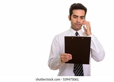 Young Persian businessman talking on mobile phone and reading clipboard