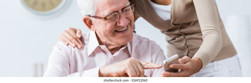 Young person is helping elder man with modern technology