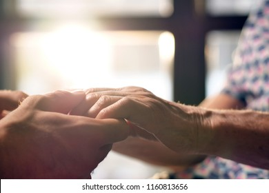 young person helps her grandmother to get up taking her hands. concept of elderly support and retirement help. help to people in need