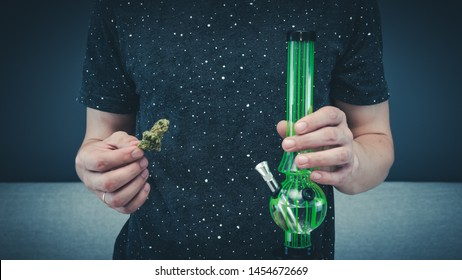 The young person hold in his hand medical marijuana buds and bong. Smoking medical cannabis with bong. Marijuana is a concept of herbal medicine