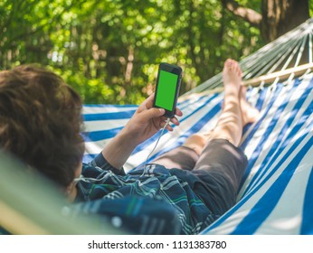young person holding phone with green chroma key lying on a hammock