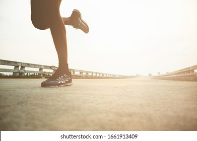 Young person is running on the sidewalk.