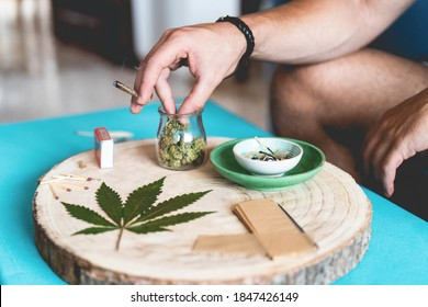 Young person smooking marijuana joint - Cannabis, stoner and weed concept - Main focus on left hand