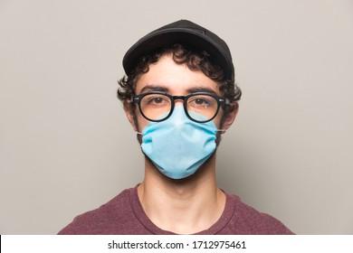 Junge Person, die einen Gesichtsmaske-Hut und eine Brille trägt