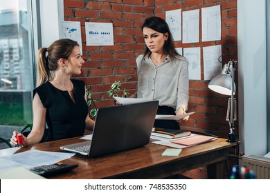 Young personal assistant discussing plans with boss in her office