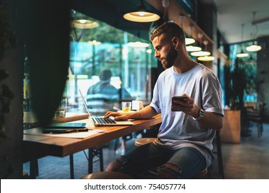 Young personal development coach answering the client by email by a laptop while having break in a coffee shop. Bearded hipster guy searching the information typed in a mobile phone on a laptop.