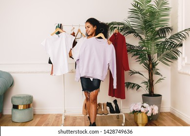 Young personal shopper holding hangers with clothes in studio