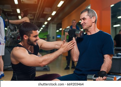 Young personal trainer working with senior man client in gym. Elderly man exercising with dumbbell. Healthy lifestyle, fitness and sports concept.