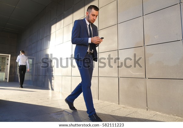 Young perspective male men, students,go to meet each other, greet one another, shake hands, talking on phone, stop and talk, walk fast step, hurry, running late on background of wall of business
