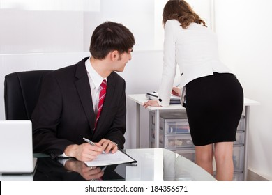 Young pervert businessman looking at businesswoman working in office