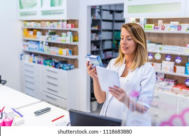 Young pharmacist holding a tablet and box of medications. Young positive brunette pharmacist woman in drug store with tablet pc. Female pharmacist with digital tablet searching for medication