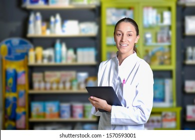 Young pharmacist standing next to medicine shelves, holding tablet
